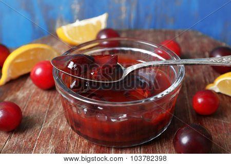 Tasty homemade plum jam in glass saucer on wooden background