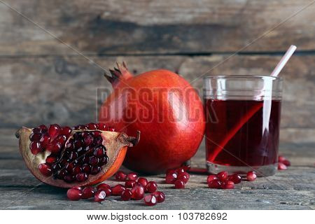 Fresh garnet juice with fruit on wooden table close up