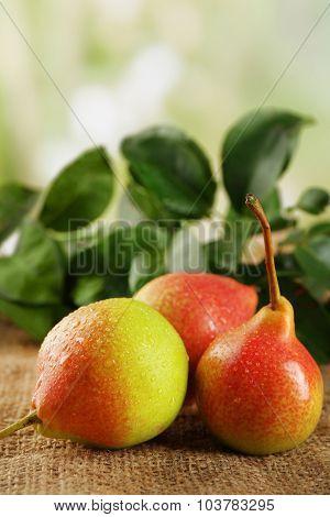 Fresh pears on sackcloth on blurred background