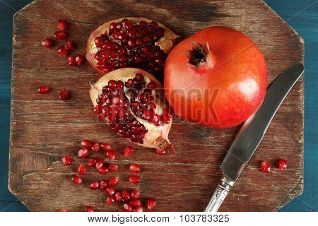 Juicy pomegranate with knife on wooden table, top view