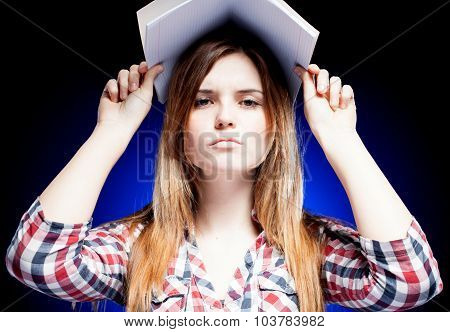 Confused And Upset Young Girl Holding Exercise Book On Her Head