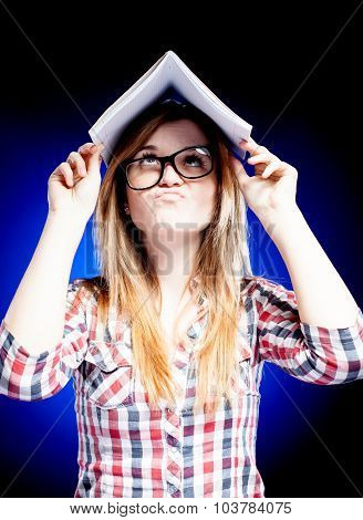 Confused Young Girl Holding Exercise Book On Her Head And Trying To Learn