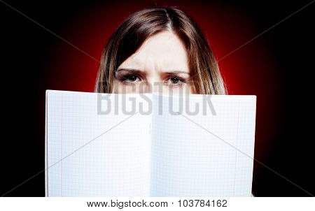 Disappointed And Sad Young Girl Holding Exercise Book