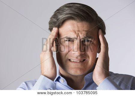 Studio Portrait Of Man Suffering With Headache