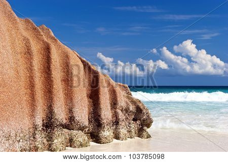 Big Granite stone on white sand beach on Indian Ocean island of Seychelles with ocean waves and blue