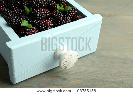 Heap of sweet blackberries with mint in box on table close up