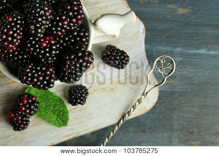 Heap of sweet blackberries with mint in cup on table close up