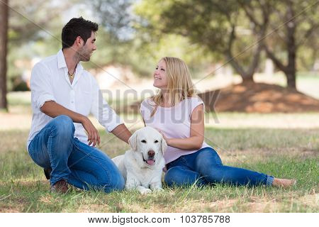 beautiful couple with old senior labrador dog in the nature