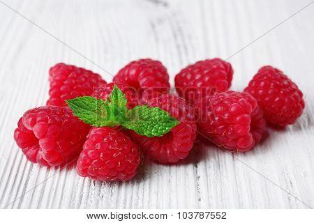 Fresh red raspberries on wooden background