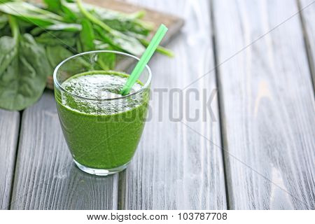 Glass of spinach juice on wooden background