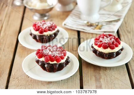 Sweet cakes with raspberries on light wooden background