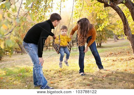 Happy young family having fun on a swing ride at a garden a autumn day