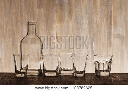 Empty Bottle And Shots On The Wooden Bar Counter