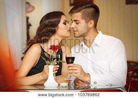 young attractive lady kisses her beloved man at the restaurant