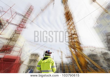 surveyor and instrument, giant building site in background, with slight zoom effect