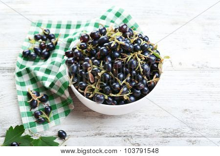 Ripe black currants in with checkered napkin on wooden background