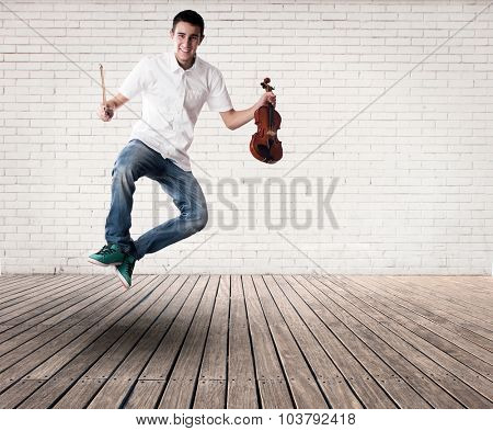 young man jumping with violin on a room