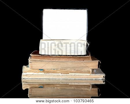 Stack Of Old Books With Blank Page Reflected