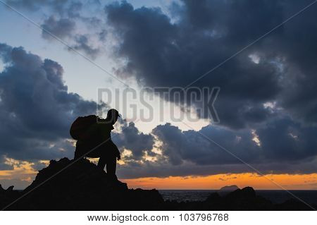 Man hiker sitting accomplish silhouette backpacker looking at inspirational ocean island landscape f