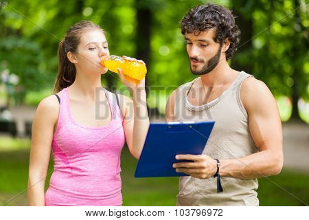 Woman drinking energy drink after running