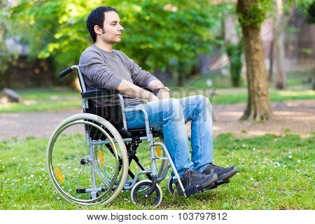 Man on a wheelchair relaxing in a park