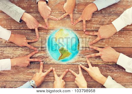 business, people, gesture and team work concept - close up of creative team showing victory hand sign and globe on table in office