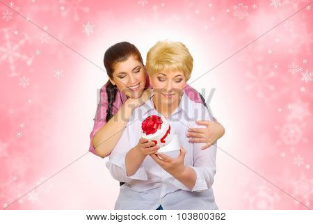 Daughter giving gift to her mother on winter background