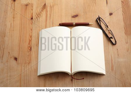 Blank Notepad with spectacles on Wooden Table. Above View.