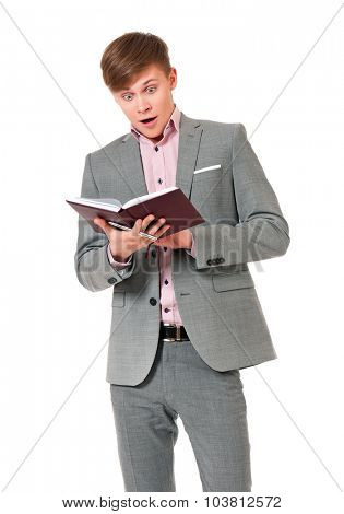 Portrait of young man in suit looking very shocked with notepad, isolated on white background