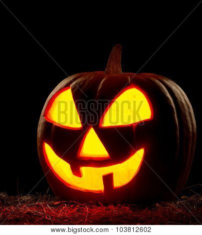 Funny Halloween pumpkin on black background. Scary glowing faces.