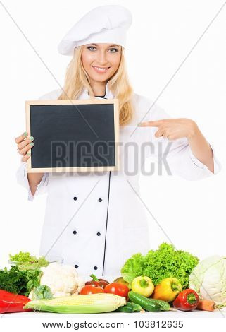 Woman cook in chef hat with small blackboard and fresh vegetables, isolated on white background