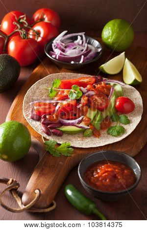 vegan taco with avocado tomato kidney beans and salsa