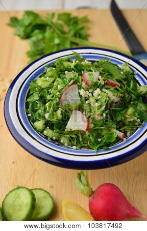 Tabouleh - a bowl of fresh middle-eastern green salad arranged with whole veggies.