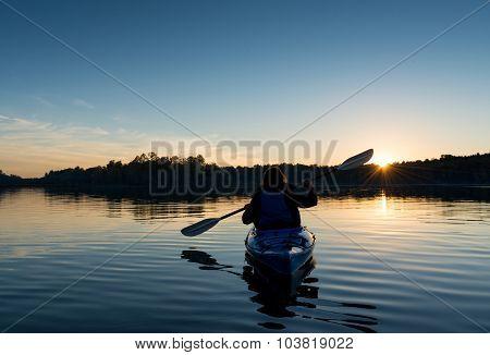 Woman Kayaking At Sunset