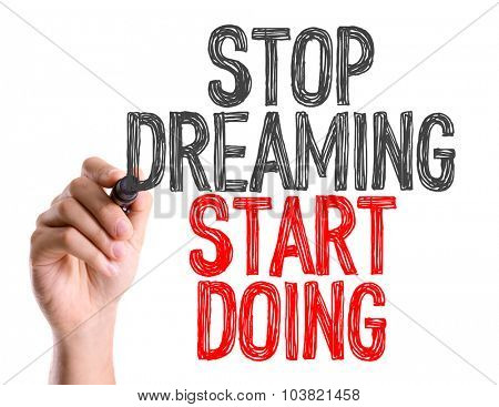 Hand with marker writing: Stop Dreaming Start Doing