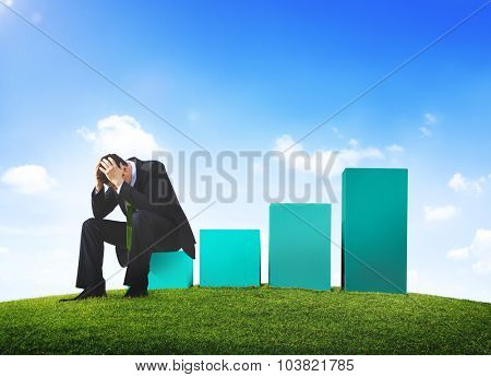 Worried Business Man Sitting on a Bar Graph