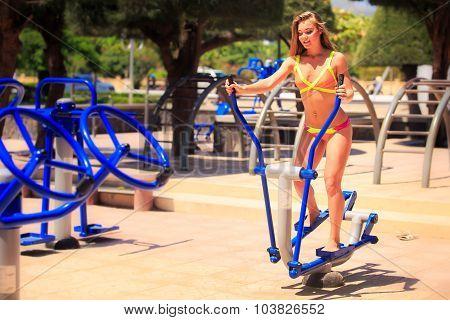 Blonde Girl In Bikini Trains On Stepper In Park Near Beach