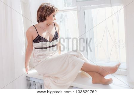 Smiling woman in nightgown looking at window