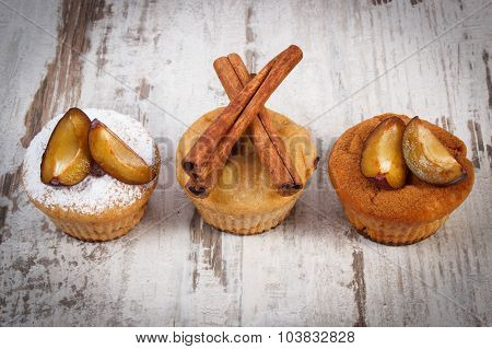 Muffins With Plums Powdered Sugar And Cinnamon On Old Wooden Background, Delicious Dessert