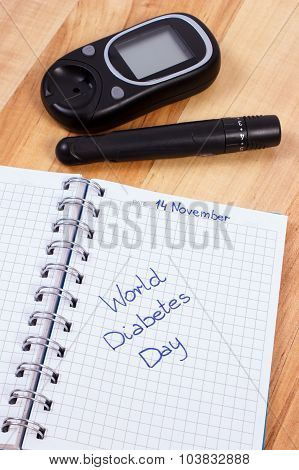 Glucometer With Lancet Device And World Diabetes Day Written In Notebook