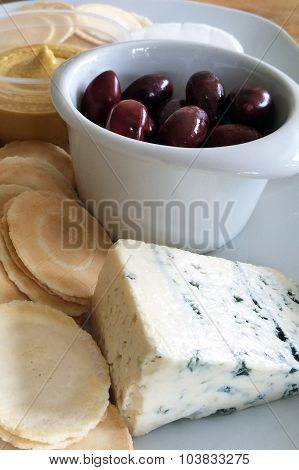 Kalamata olives served as appetisers with blue vein cheese crackers and humus.