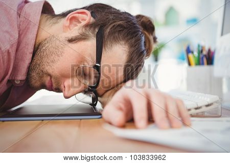 Businessman wearing eye glasses resting with head on desk in office
