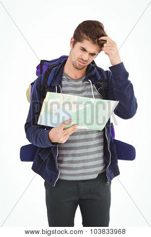 Man scratching head while looking in map standing against white background