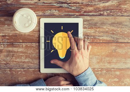 business, education, inspiration, people and technology concept - close up of male hands with lighting bulb icon on tablet pc computer screen and coffee cup at table