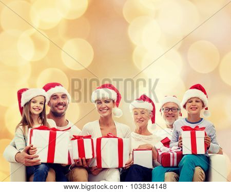 family, happiness, generation, holidays and people concept - happy family in santa helper hats with gift boxes sitting on couch over beige lights background