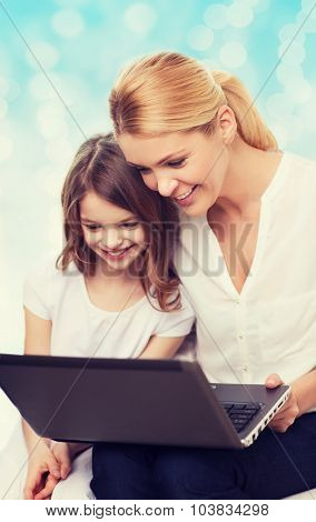 family, childhood, holidays, technology and people concept - smiling mother and little girl with laptop computer over blue lights background