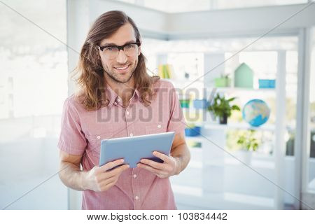 Portrait of confident hipster holding digital tablet standing in office