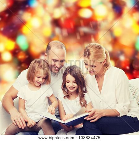 family, childhood, holidays and people - smiling mother, father and little girls reading book over red lights background