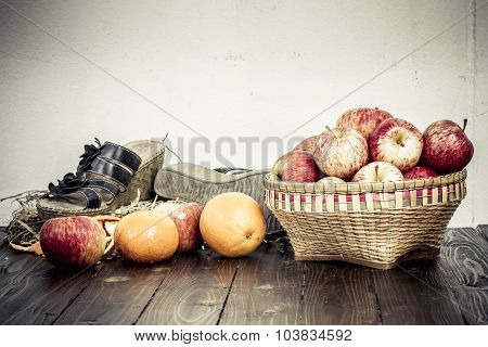 Apple In Bamboo Basket And Oranges On Wooden Table
