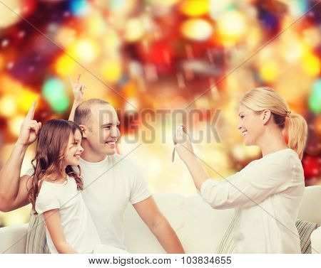 family, holidays, technology and people concept - smiling mother, father and little girl with camera over red lights background